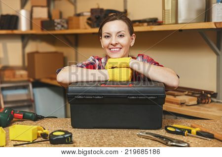 Beautiful smiling caucasian young brown-hair woman in plaid shirt gray T-shirt yellow gloves working in carpentry workshop at wooden table place with black toolbox different tools. Gender equality poster