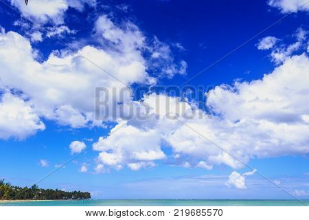 Cumulus humilis clouds on blue sky above the sea and coast. Nature background