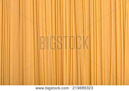 Yellow long spaghetti. Thin pasta arranged in rows. Italian pasta. Long spaghetti. Raw spaghetti wallpaper. Thin spaghetti.Italian cuisine.