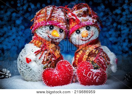 Love snowmen. Snowfall. Snow background. Love concept. Valentine's Day Greeting card with copy-space. Snowmen love couple set against each other on Christmas background