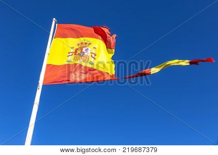 Close-up torn Spanish flag waving on the wind on the mast over clear blue sky background