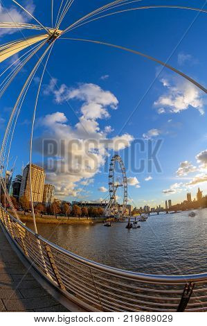 LONDON ENGLAND - NOVEMBER 28 2017: View with famous London Eye from Golden Jubilee bridges cross the River Thames. Sunset time.