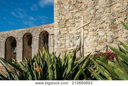 Bird of paradise flowers frame the statue of Junipero Serra at San Juan Capistrano mission
