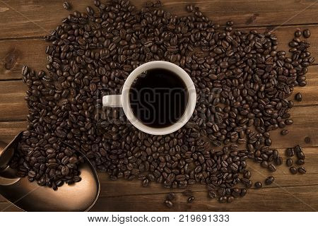 Cup of coffee and coffee beans on old wooden background. Directly above.