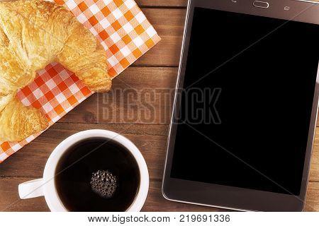 Morning coffee cup with digital tablet for business work directly above.