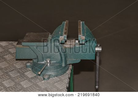 The grinded metal vise is fixed to the table an instrument for working in the industry