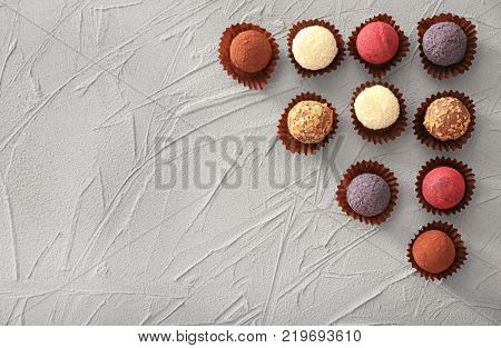 Assorted chocolate truffles on textured background