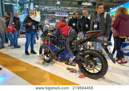 MILAN, ITALY - NOVEMBER 11, 2017: a visitor try out a motorcycle at the EICMA 2017 - 75th International Motorcycle Exhibition.