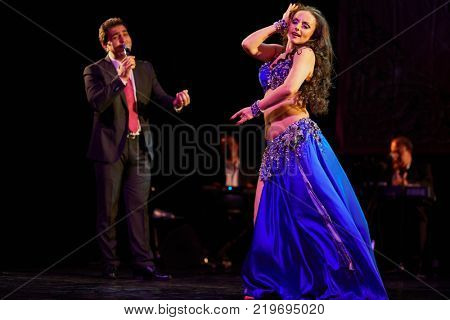 MOSCOW, RUSSIA - OCT 21, 2017: Bellydancer, Yasser Alama and orchestra on stage of Luna Theatre during Gala Concert after 12th international festival of oriental dance ASSEMBLY 2017.
