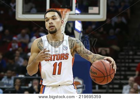 NEWARK, NJ - DEC 9: Florida Gators guard Chris Chiozza (11) looks to pass the ball during the game against the Cincinnati Bearcats on December 9, 2017 at the Prudential Center in Newark, New Jersey.