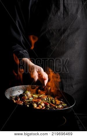 Chef cooking vegetables on a pan with fire. Black background for copy text. Vertical photo for banner design.