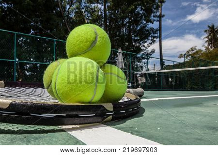 Tennis balls and racket in tennis court outdoors