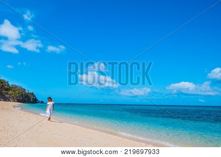Woman in a white dress is walking on the blue sea beach background
