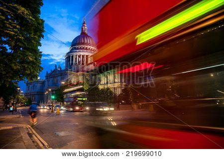London cityscape with Double Decker bus moves along the Cannon Street near St Paul's Cathedral in twilight