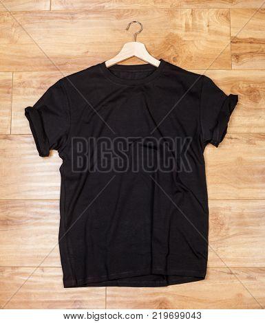 Wrinkled black plain short sleeved cotton T-Shirt on a planket wooden background