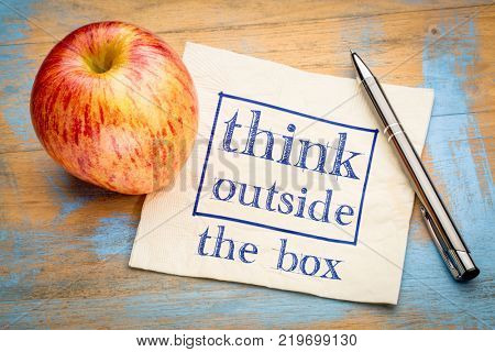Think outside the box concept - handwriting on a napkin with an apple