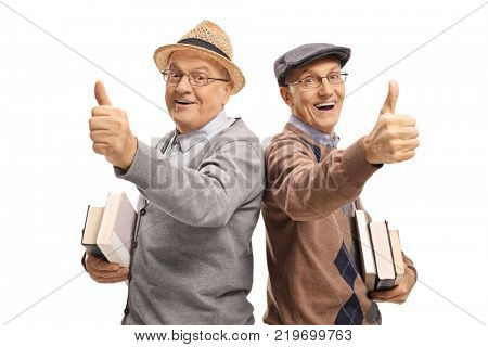 Two cheerful elderly men with books making thumb up gestures isolated on white background