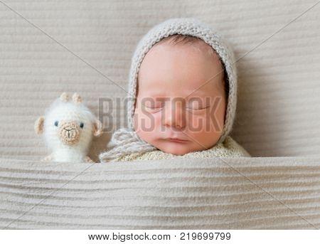 Portrait of little baby boy sleeping under blanket, top view.