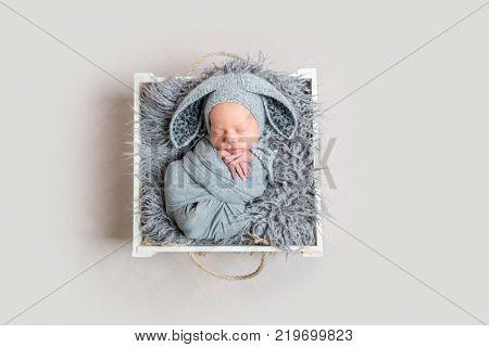 Cute newborn boy sleeps on wooden box, top view
