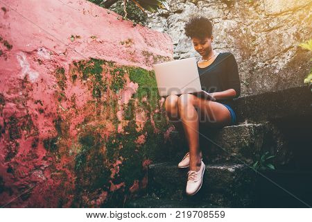 Young lovely Brazilian female student is sitting on a stony staircase near reddish mossy wall with laptop; cute black undergraduate girl with net-book on a step of stone stairs is making her homework