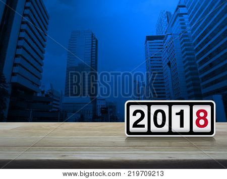 Retro flip clock with 2018 text on wooden table over modern city tower Happy new year concept