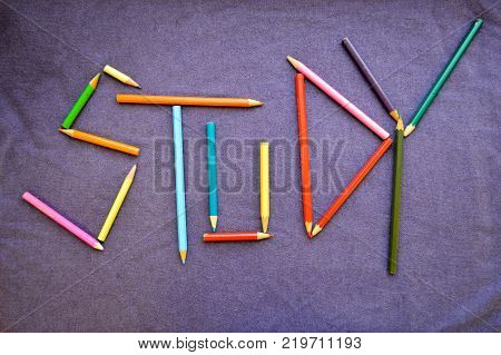 Write a study written in colored pencils. The inscription study is made up of colored pencils. The word study is composed of colored multicolored pencils against the background of a purple cloth.