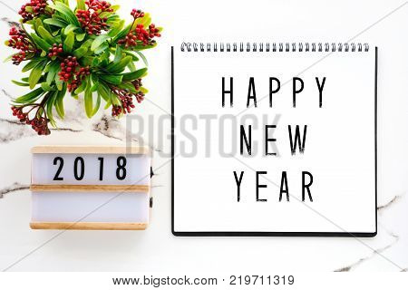 2018 new year greeting card 2018 on wood box and happy new year on notebook paper over white marble background banner top view