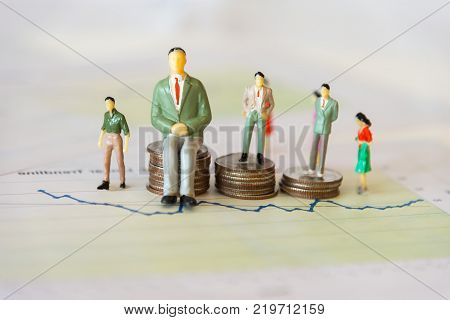 Miniature group businessman standing on money coin stack growing finance graph with project for presenting investment. Investment and Business Concept.