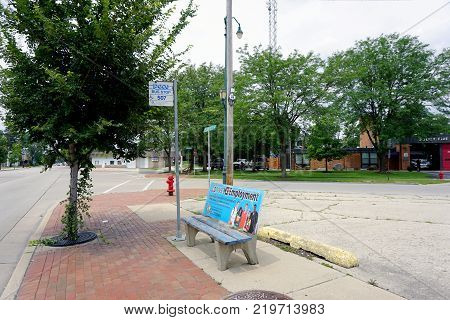 JOLIET, ILLINOIS / UNITED STATES - JULY 26, 2017: Bus passengers may sit on a bench while waiting for the bus to arrive, at PACE Bus Stop 507, on Plainfield Road.