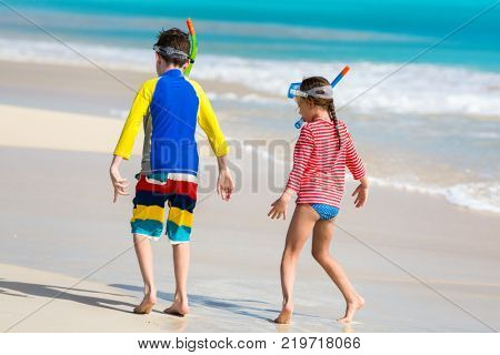 Little kids in rash guards for sun protection with snorkeling equipment on tropical beach having fun during summer vacation poster