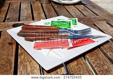 VICTORIA, GOZO, MALTA - APRIL 3, 2017 - Cutlery with sachets of ketchup and mayonnaise on a wooden table within the citadel Victoria (Rabat) Gozo Malta Europe, April 3, 2017.