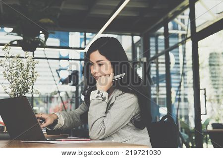 young woman holding a credit card and using laptop computer for online shopping at cafe. businesswoman purchase goods from internet at office. female adult make payment on bank website at workplace