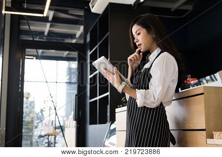 small business owner holding tablet at counter in coffee shop. asian female barista wearing apron using touchpad at bar in cafe. food service restaurant entrepreneur concept.