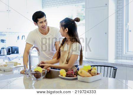 Beautiful asian young couple is looking to cooking in kitchen at homeHappy young woman washing vegetables in the sink and handsome man standing next to her.