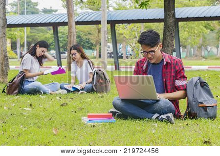 Group of university asian students having fun outdoorsMan using laptop computer at university high school campuscollege in summer holiday relaxation.