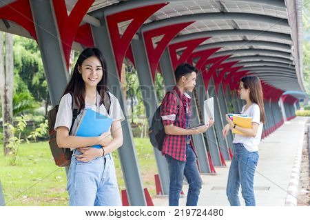 Group of university asian students having fun outdoorsWoman holding many books at university high school campuscollege in summer holiday relaxation.