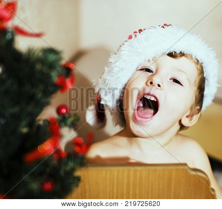 portrait of little cute boy in Christmas in red hat at home emotional