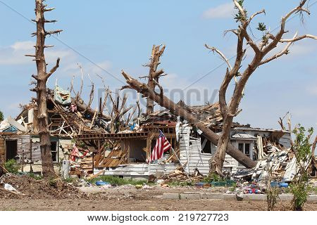 An American Flag tells viewers that the owner of this home refuse to give in to the power of nature and the Ef5 tornado that cause this kind of damage, making their home and the stately trees that surrounded it unrecognizable!