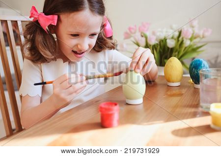 happy 7 years old kid girl painting easter eggs. Easter craft and holiday preparations at home.