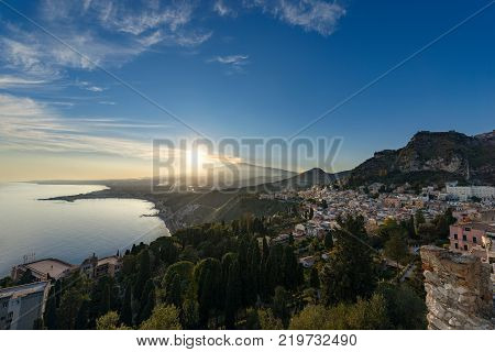 The mount Etna Volcano with smoke and the Taormina town Messina Sicily island Italy (Sicilia Italia)