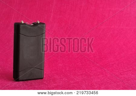 A black taser isolated against a pink background