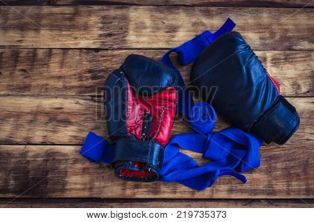 Old Black Boxing Gloves On  Vintage Wooden Grunge Background Copy Space.