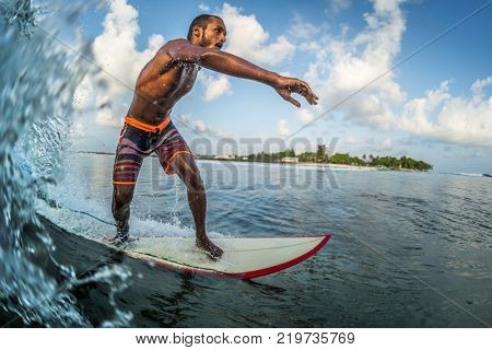 Asian professional surfer rides the ocean wave on a short board. Extreme sport and active lifestyle concept
