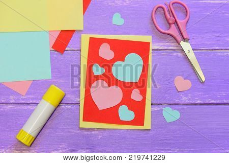 Valentines day greeting card, scissirs, glue stick, colored paper sheets and hearts on a wooden table. Valentines day paper greeting card for kids. Top view