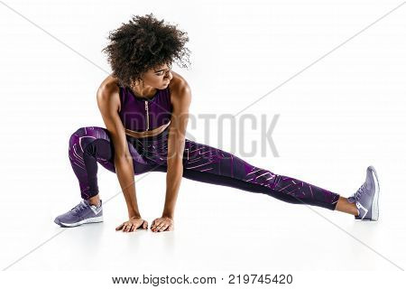 Beautiful young girl stretching her hamstrings. Photo of sporty girl doing exercising on white background. Sports