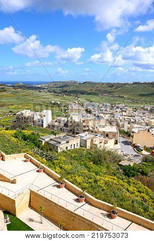 Elevated view of fortified buildings and the landscaped old moat within the citadel with views over the town rooftops towards the countryside and sea Victoria (Rabat) Gozo Malta Europe.