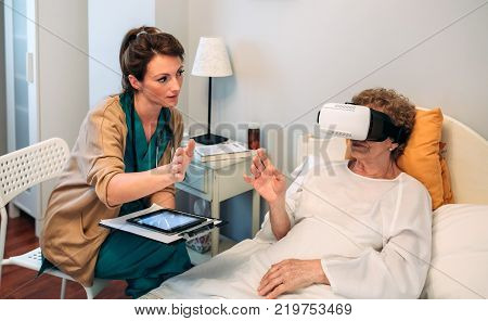 Older patient using virtual reality glasses to see her spine while female doctor explains