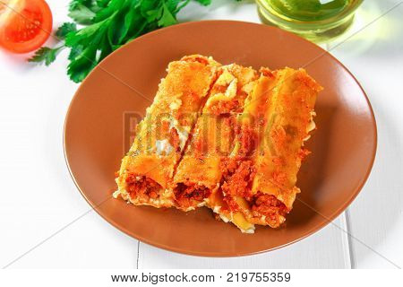 Traditional Italian pasta cannelloni. Baked tubes stuffed with minced meat with parmesan cheese and bechamel sauce on a white wooden table