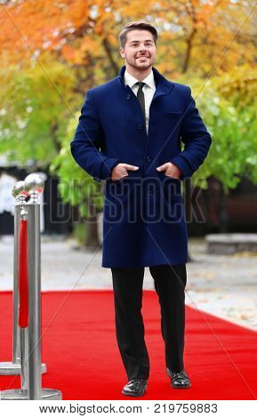 Handsome young man in black suit on red carpet, outdoors
