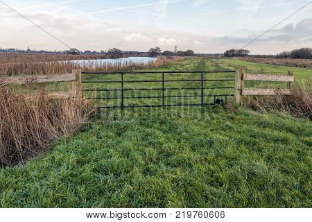 Steel gate in a Dutch meadow next to a narrow river in the polder. It is at the end of a cloudy day in the fall season.